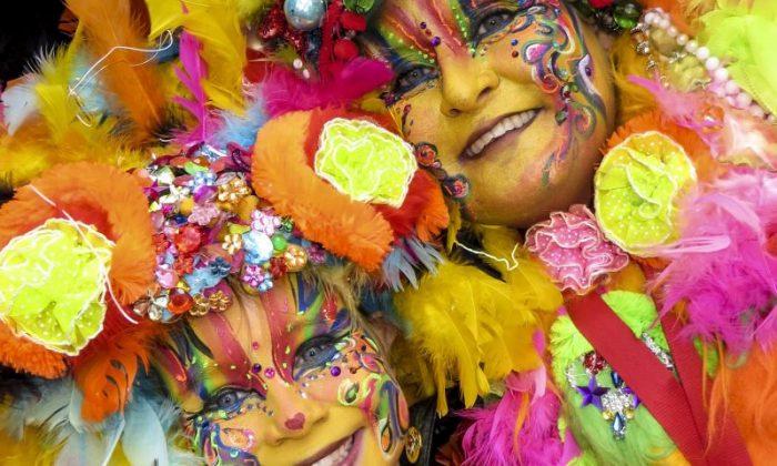 Duas mulheres com fantasias e roupas bem coloridas mostram como é o Carnaval em Maastricht, na Holanda