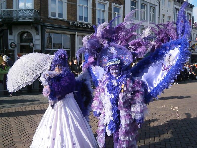 Casal fantasiado de roxo e branco, com plumas e maquiagem, no carnaval da Holanda, em Maastricht