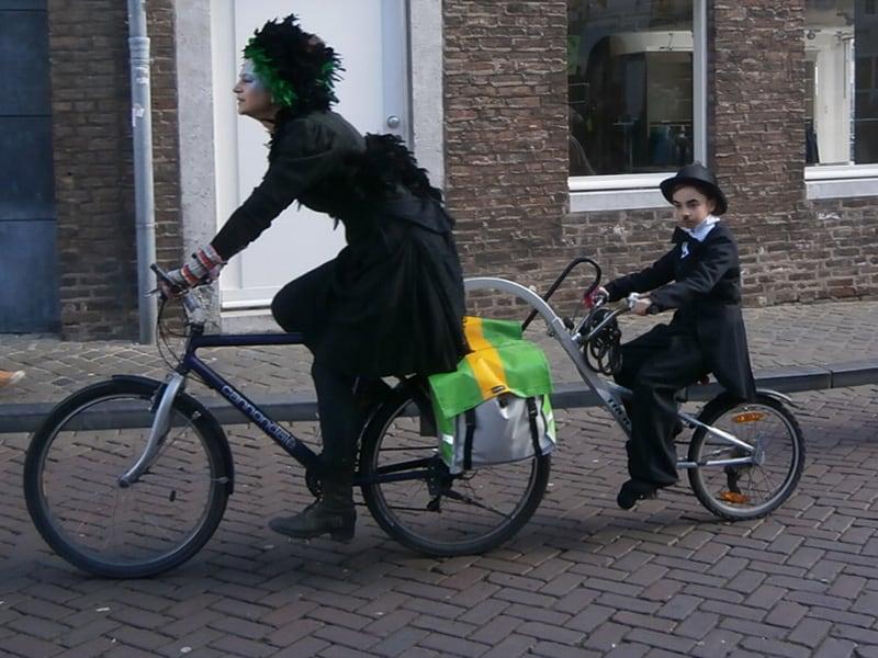 Mãe e filho fantasiados, cada um na sua bicicleta, indo para o Carnaval em Maastricht