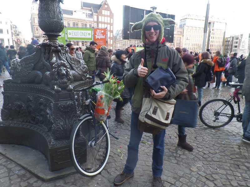Dia da Tulipa na Praça Dam em Amsterdam,na Holanda. Rapaz vestido de Mestre Yoda leva as tulipas na sua bicicleta
