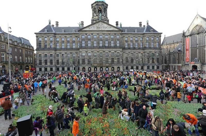 Dia da Tulipa na Holanda visitantes pegam tulipas no jardim montado na Praça Dam em Amsterdã