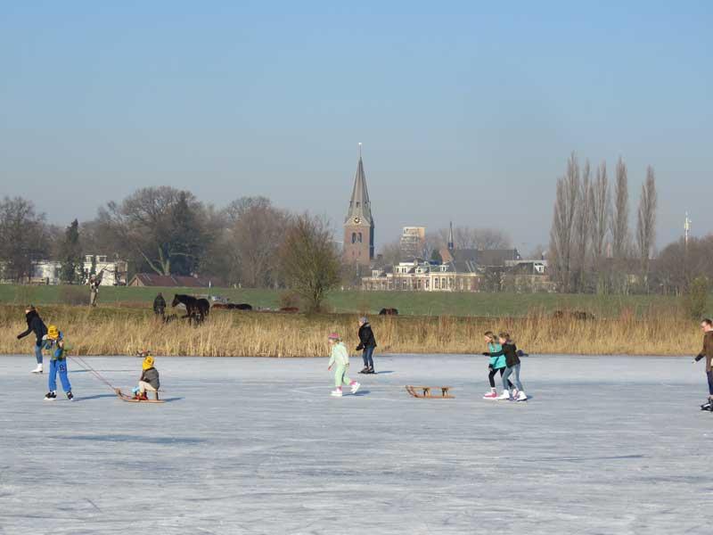 Crianças brincam em pista de patinação no gelo ao ar livre enquanto puxam trenó. Ao fundo, a cidade de Wageningen na Holanda.