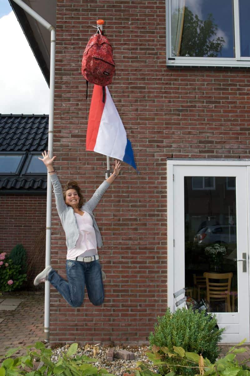 Garota pulando e comemorando porque passou nos exames finais do ensino médio na Holanda, junto da bandeira holandesa e da mochila pendurada