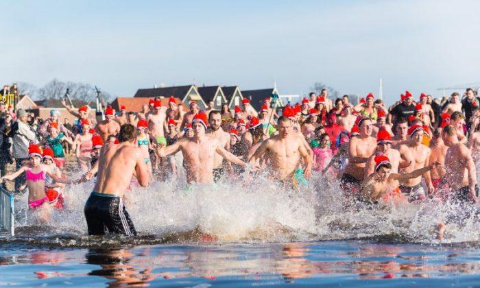 holandeses fazendo o tradicional mergulho de ano novo no mar gelado da Holanda