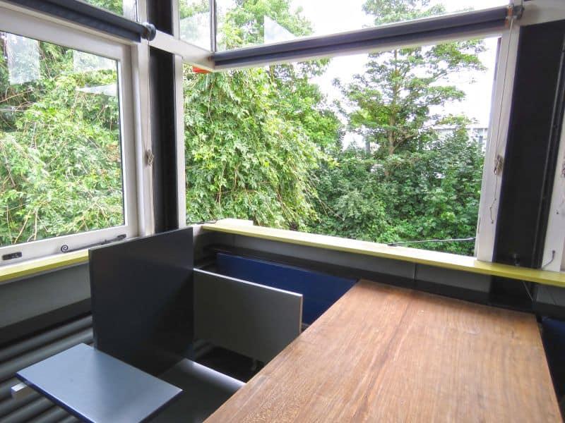 A janela invisível da Casa Rietveld Schroder em Utrecht, na Holanda. Em frente à mesa, a Berlin Chair, também de autoria do Rietveld.