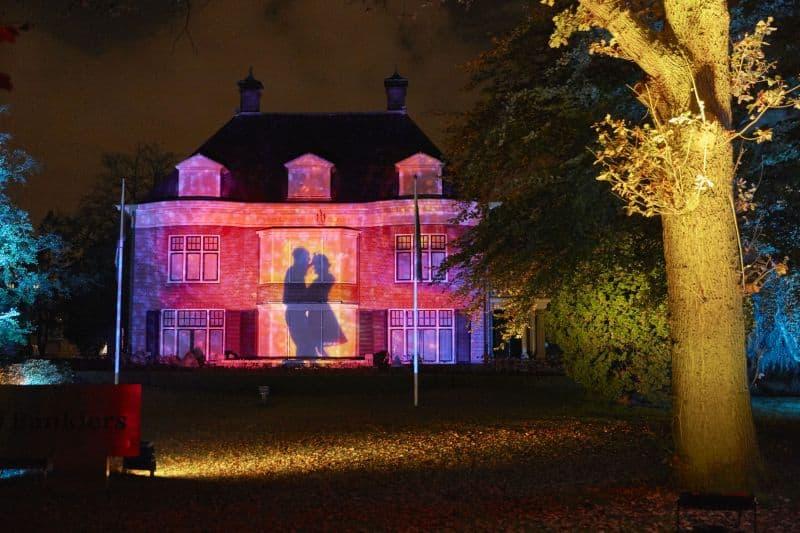 Projeção de luz em uma casa com casal dançando durante o Festival Glow Eindhoven, na Holanda