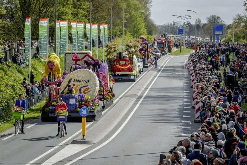 Desfile de carro alegóricos decorados com flores e multidão assistindo ao Bloemencorso Bollenstreek, também conhecido como a Parada de Flores do Keukenhof