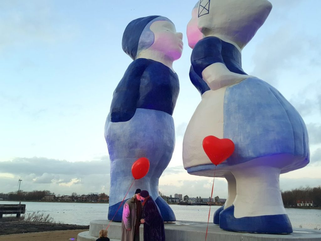 Casal de idosos se beija em frente à estátua gigante do casal holandês que fica em Amsterdam, na Holanda