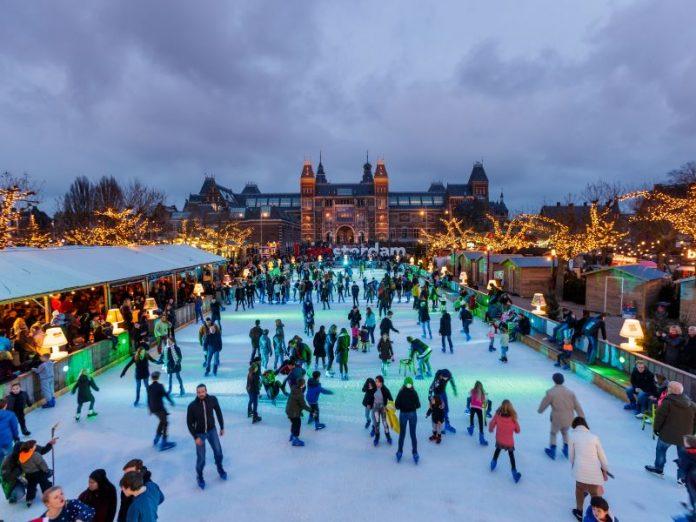 Noite no Mercado de Natal que acontece em frente ao Rijksmuseum em Amsterdam, com pista de patinação de gelo.