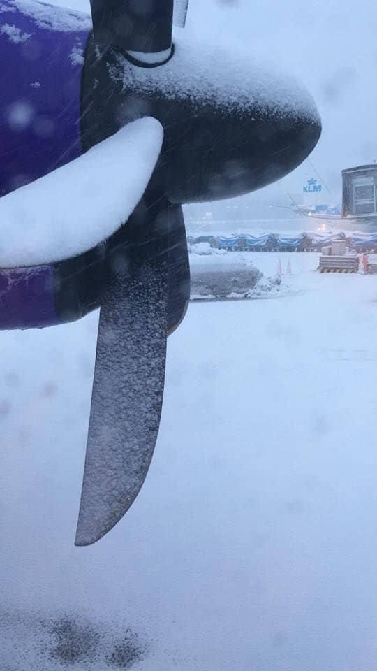 Hélice de avião e pista de pouso do Aeroporto Schiphol, de Amsterdam na Holanda, cobertos de neve.