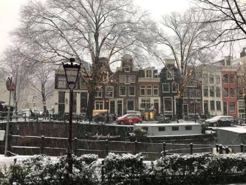 casas típicas de amsterdam cobertas pela neve, à beira de um canal