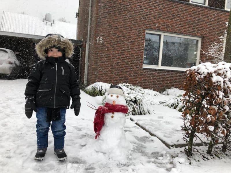 Criança toda agasalhada com casaco e luvas posa ao lado de um boneco de neve em Eindhoven, na Holanda