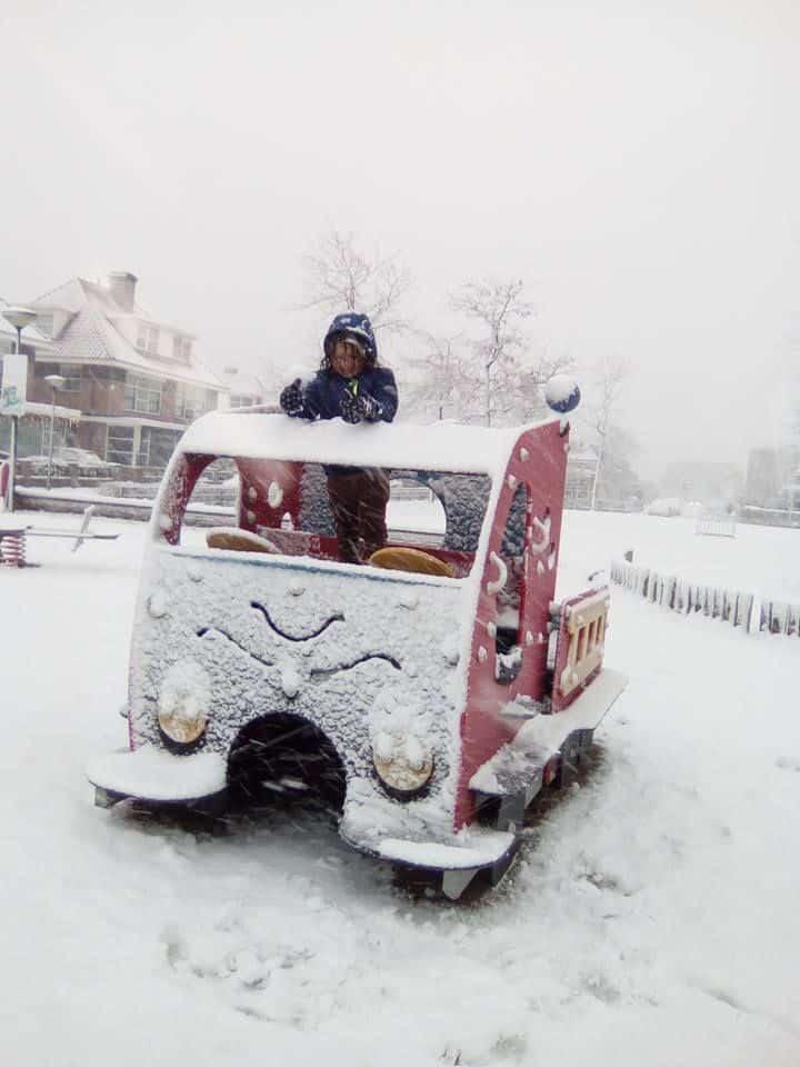 criança brinca dentro de carro cercada por neve em Haia, na Holanda