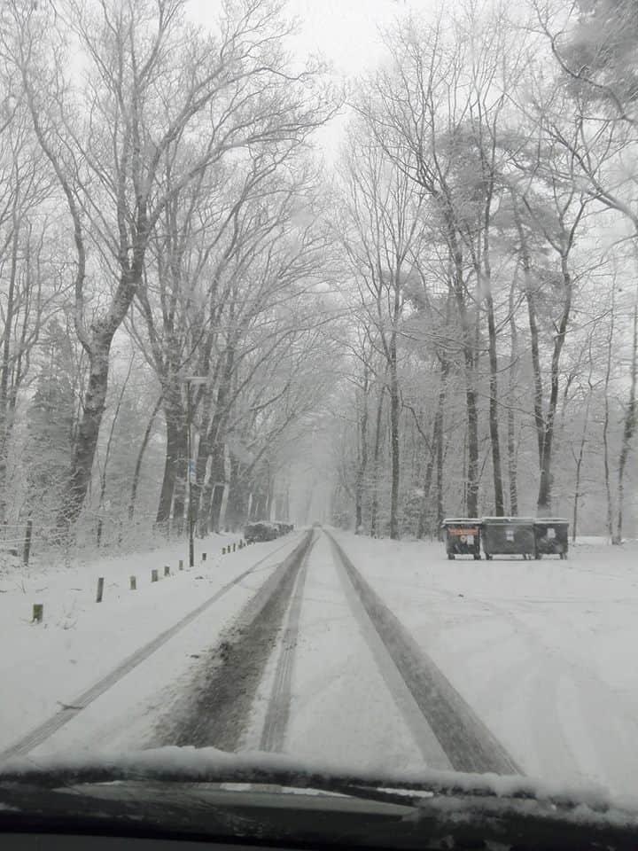 Carro dirigindo por estrada cheia de neve em Oisterwijk, na Holanda, durante o inverno