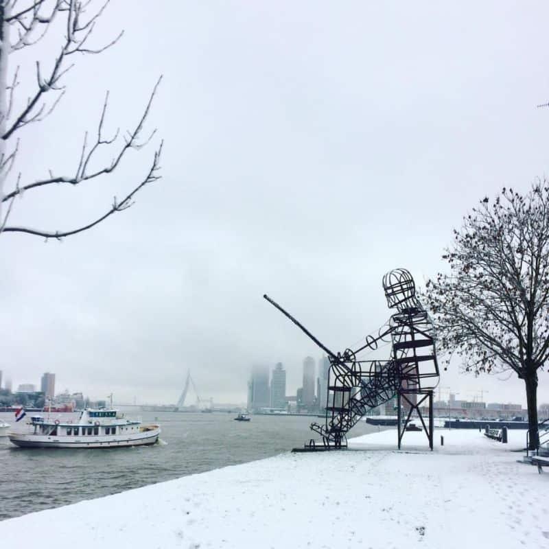 ponte erasmus em Rotterdam debaixo de neve, com a escultura De Visser em primeiro plano
