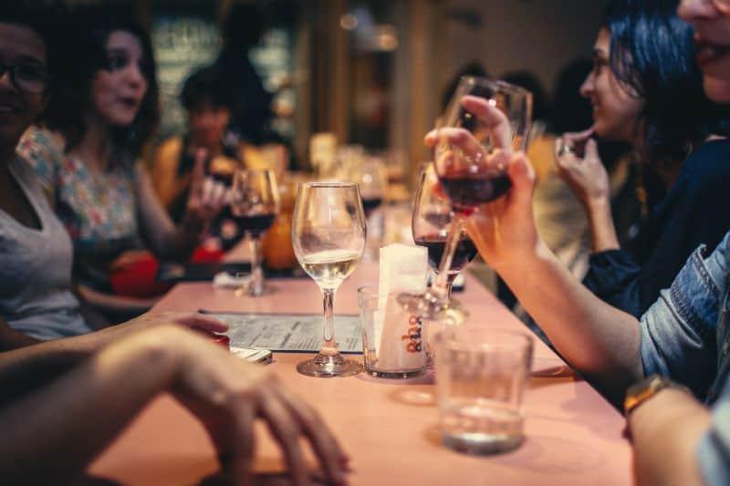 pessoas reunidas em um bar confraternizando, bebendo vinho e outras bebidas
