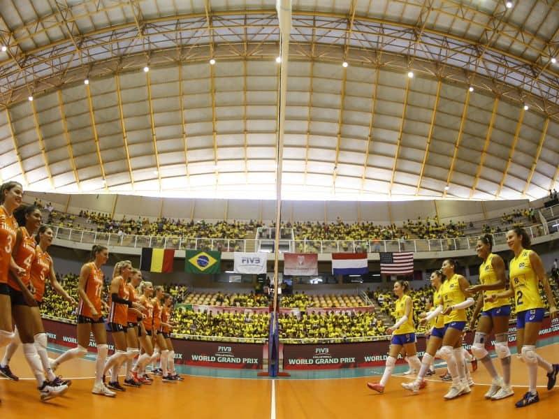 equipes da seleção feminina de vôlei do Brasil e da Holanda se apresentam em quadra para jogar.