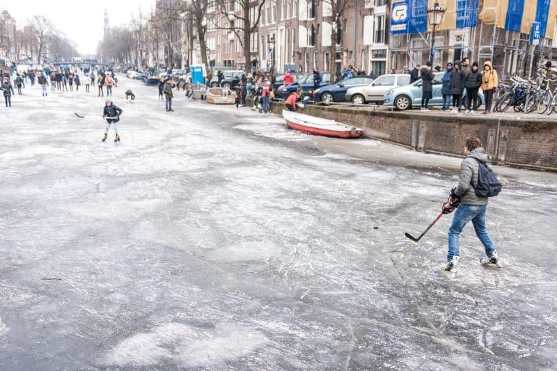 Canal em Amsterdam na Holanda congelado e pessoas jogam hockey no gelo em cima do canal
