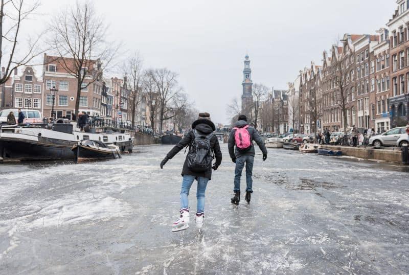 Casal patina sobre o gelo no Prinsengracht, famoso canal de Amsterdam que ficou congelado devido ao intenso inverno europeu. O local fica próximo à Casa da Anne Frank.