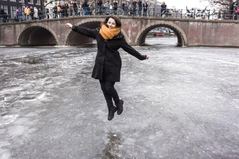 Garota pula no Canal em Amsterdam que está congelado devido ao intenso inverno na Holanda