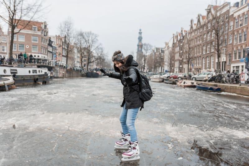 garota escorrega no gelo do canal de Amsterdam na Holanda que está congelado devido ao intenso inverno europeu