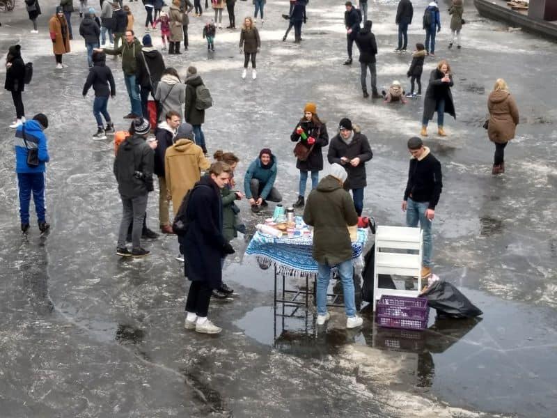 Canal em Amsterdam na Holanda fica congelado e as pessoas andam sobre o gelo e vendem bebidas e biscoitos em cima do canal