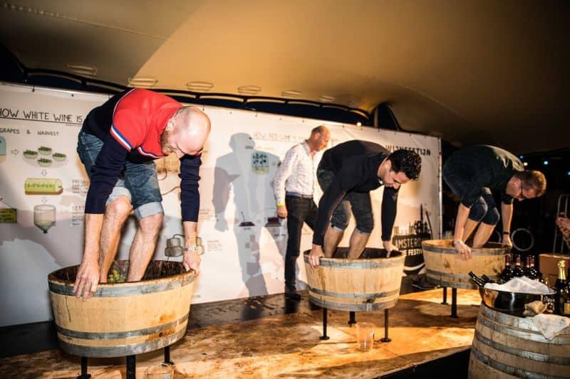 homens competem na prensa da uva. eles pisam nas uvas durante o festival de vinho de amsterdã, o amsterdam wine festival