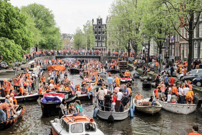 No Dia do Rei, barcos passeiam com pessoas comemorando nos canais de Amsterdam