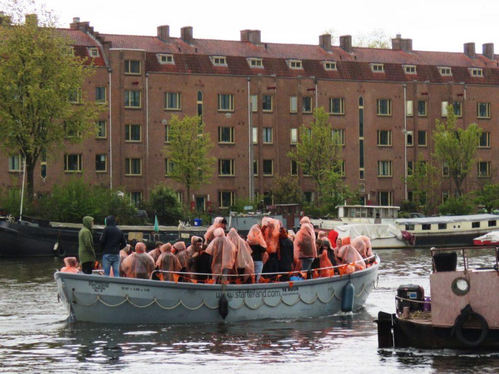 pessoas no barco com capa de chuva laranja comemoram o dia do rei nos canais de amsterdam, na Holanda