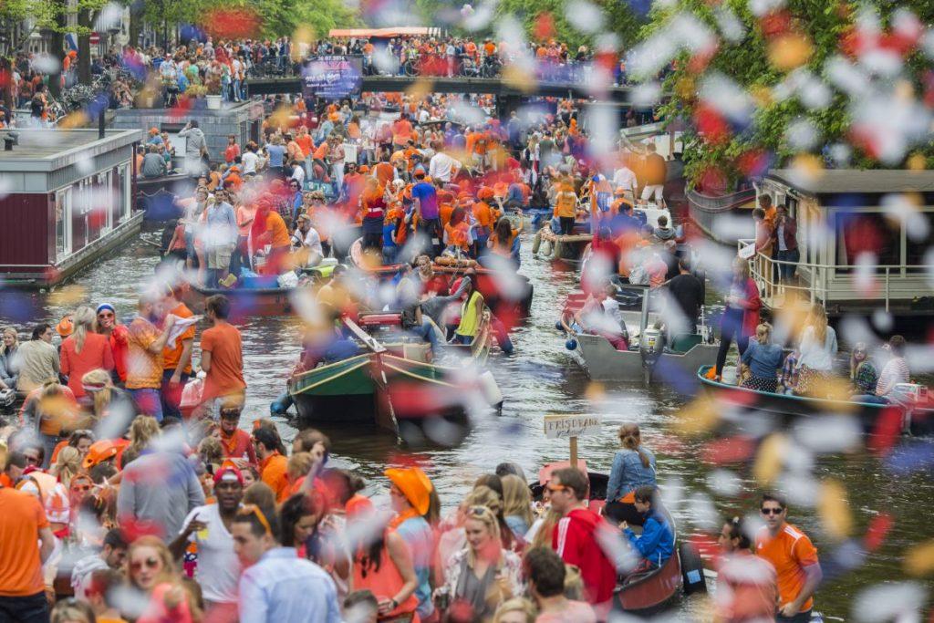 Dia do Rei na Holanda. Milhares de pessoas comemoram nos barcos dos canais de Amsterdam.