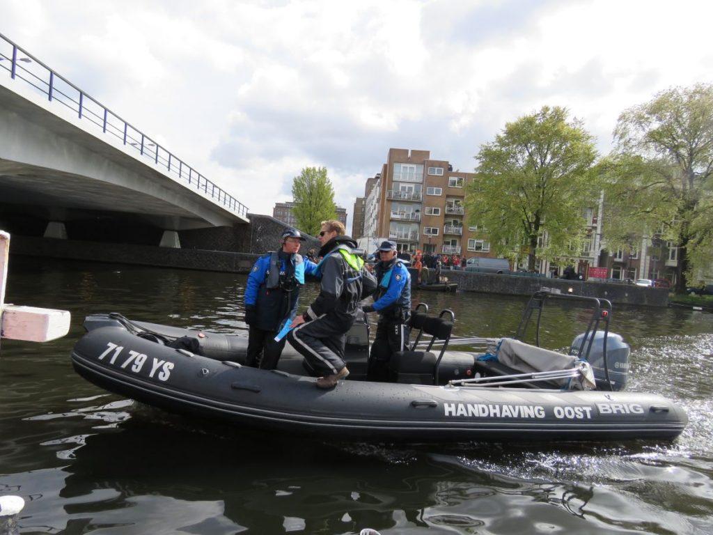 barco da polícia nos canais de amsterdam durante o dia do rei na holanda