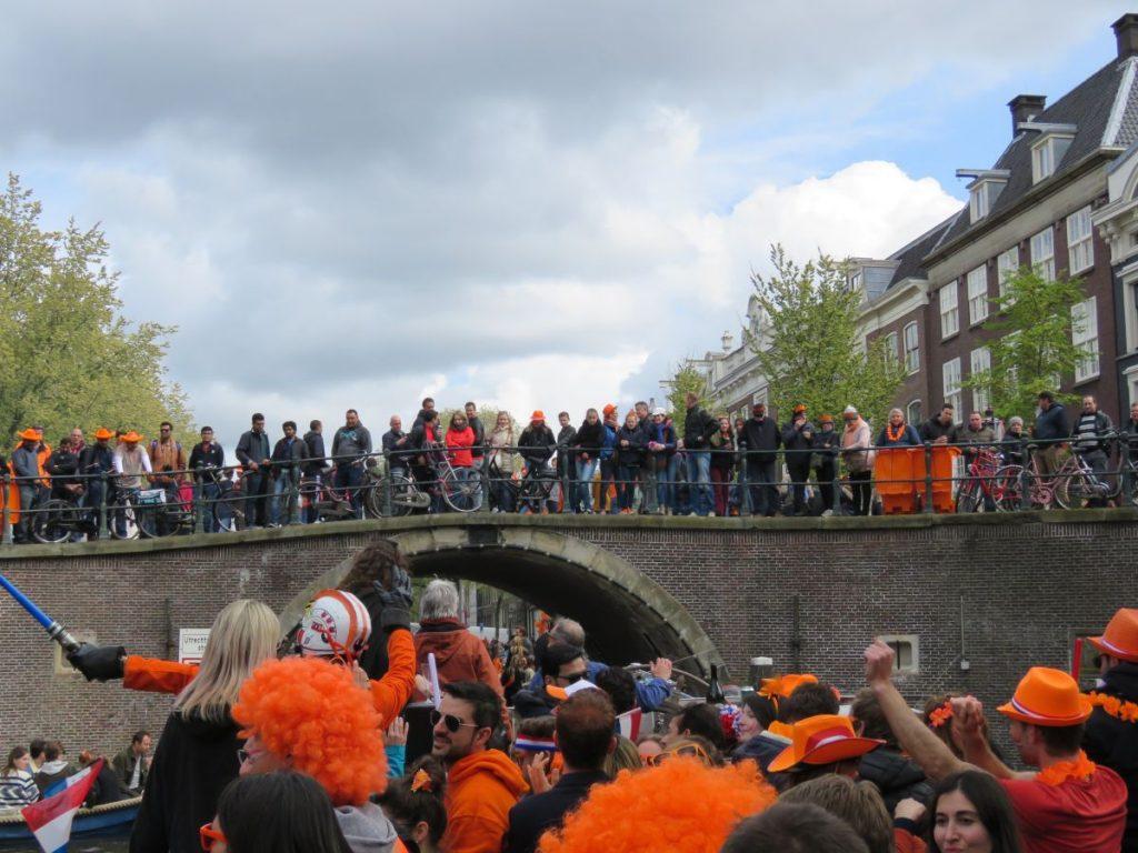 Dia do Rei em Amsterdam. Pessoas assistem em cima da ponte barco passando com pessoas comemorando a festa na Holanda