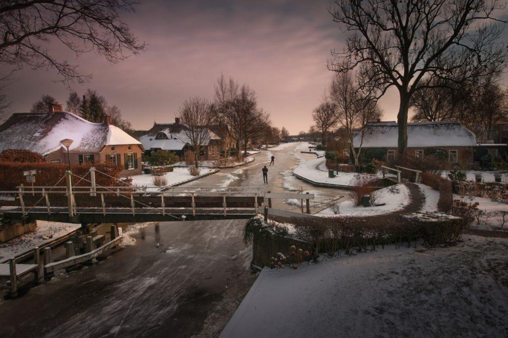 Giethoorn no inverno: casas ficam cobertas de neve e os canais congelam e se transformam em uma enorme pista de patinação no gelo
